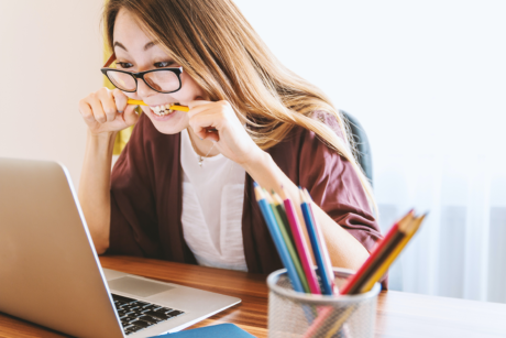 frustrated-woman-chewing-a-pencil-in-front-of-her-laptop